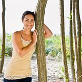 Woman leaning on tree at beach