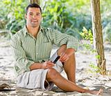 Man text messaging on cell phone at beach