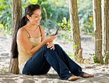 Woman text messaging on cell phone at beach