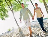 Couple walking holding hands at beach