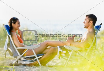 Boyfriend giving girlfriend foot massage at beach
