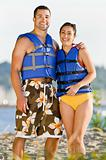 Couple wearing life jackets at beach