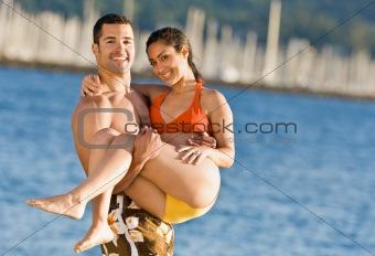 Boyfriend carrying girlfriend at beach