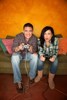 Attractive Hispanic Couple Playing a Video Game with Handheld Controllers