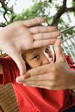 Boy Looking Through Hands