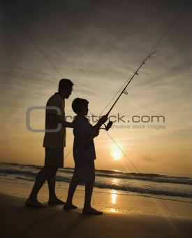 Man and young boy fishing in surf Man and young boy fishing in surf Man and young boy fishing in surf