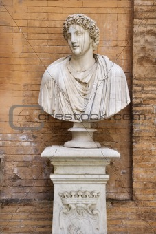 Carved Bust In Front of Brick Wall