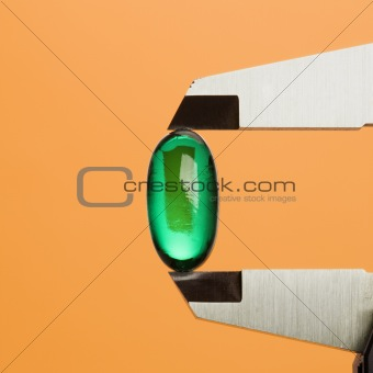 Green Capsule in Caliper. Isolated