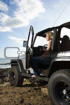 Woman Sitting in an SUV at the Beach