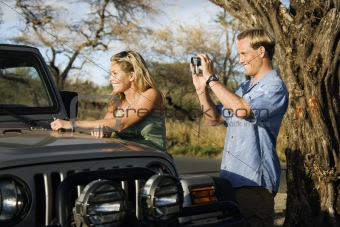 Tourist Couple Standing By Car