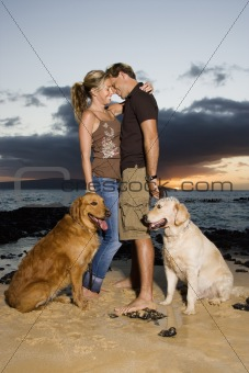 Affectionate Couple With Dogs at the Beach