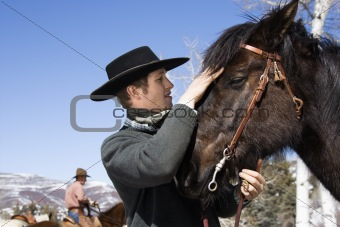 Attractive Young Man Petting Horse