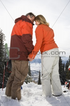 Ski Couple in Snow Holding Hands