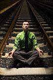 Businessman Meditating on Railroad Tracks.