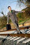 Businessman Walking on Railroad Tracks