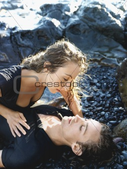 Attractive Young Couple Lying on Rocks
