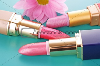 Three new lipsticks and pink flower on blue background