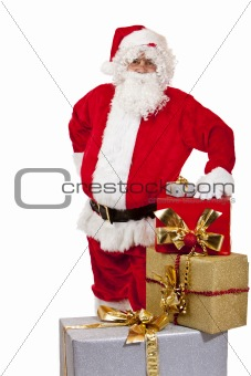 Santa Claus standing behind Christmas gift boxes and leaning on