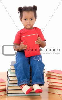Baby reading sitting on a pile of books