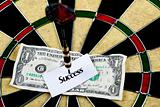 Darts target and dollar in bull's-eye
