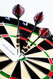 Dartboard with three darts in a bulls eye