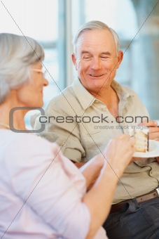 A senior woman giving a slice of cake to her happy husband