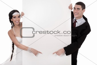 Bride and groom pointing at blank board