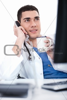 Portrait of young doctor talking over telephone and having coffee
