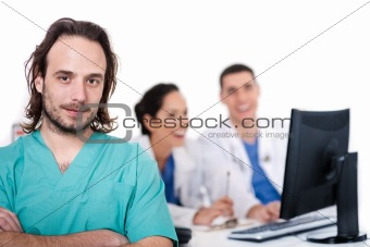 Male doctor on focus, two doctors discussing at background
