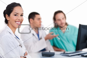 Smiling young doctor with other doctors behind her