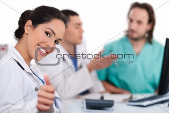 Asian women doctor show ok sign, two other team mates talking deeply
