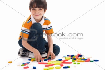 Adorable caucasian boy joining the blocks while playing