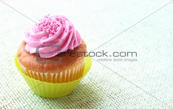 Small vanilla cupcake with strawberry icing