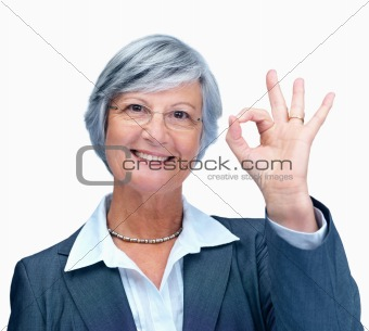 Happy elderly business woman showing a positive gesture