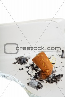 cigarette on a broken ashtray isolated on white
