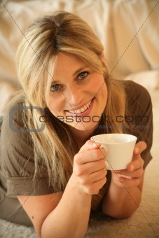 Portrait of Young Woman Having a Cup of Coffee, Lying on Floor