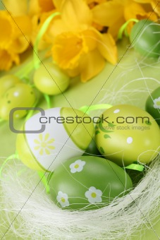 Green Easter eggs and yellow daffodils