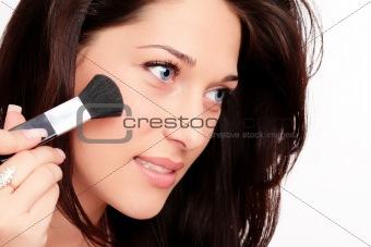 Beautiful brunette woman doing makeup