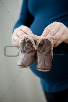 Pregnant mother holding baby booties
