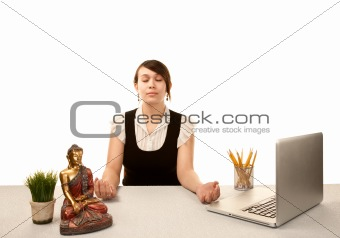 Pretty young woman meditating at her desk