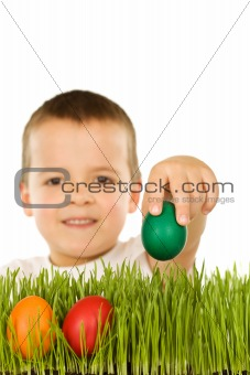 Boy putting colorful easter eggs in the grass