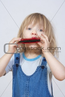 boy with long blond hair playing harmonica