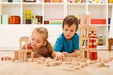 Kids inspecting their wooden block buildings