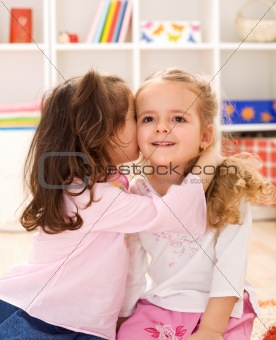 Little girls sharing a delightful secret