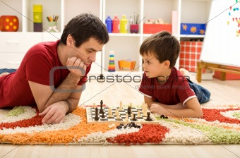 Man teaching boy the rules of chess