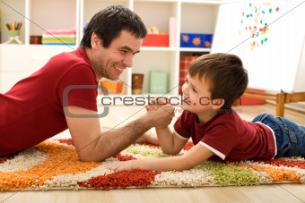 Happy kid and his father arm wrestling
