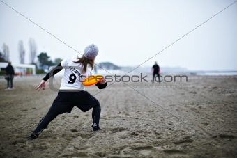 A girl playing a game of frisbee on the beach
