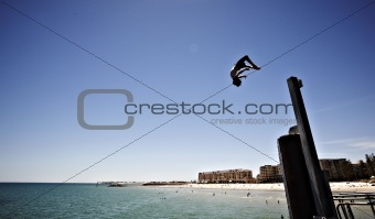 Boy doing a back flip off a pier into the sea