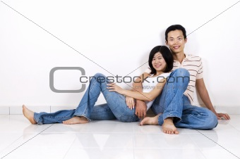 Couple sitting on floor at home.