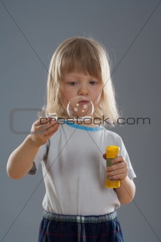 boy with long blond hair looking at big soap bubble - isolated on gray